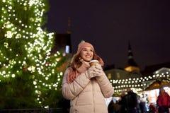 Den lyckliga unga kvinnan med kaffe på jul marknadsför Royaltyfri Bild