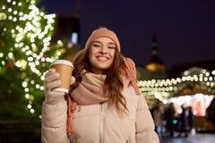Den lyckliga unga kvinnan med kaffe på jul marknadsför Royaltyfri Fotografi