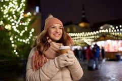 Den lyckliga unga kvinnan med kaffe på jul marknadsför Royaltyfri Foto