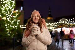 Den lyckliga unga kvinnan med kaffe på jul marknadsför arkivfoto