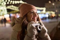 Den lyckliga unga kvinnan med kameran på jul marknadsför Royaltyfri Bild