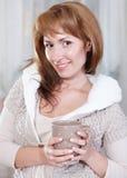 Den lyckliga unga kvinnan med kuper av tea (eller kaffe) Royaltyfri Foto