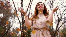Den lyckliga unga kvinnan med rött lockigt hår som kastar sidor i en höstnedgång, parkerar Arkivbild
