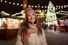 Den lyckliga unga kvinnan på jul marknadsför i vinter Arkivfoton