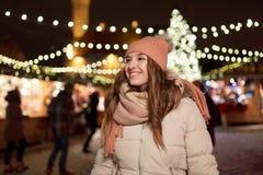 Den lyckliga unga kvinnan på jul marknadsför i vinter Arkivbilder