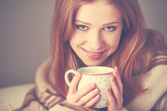 Den lyckliga unga kvinnan är under en filt och en kopp kaffe på vintermorgon hemma Royaltyfri Bild