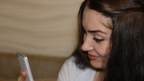 Den lyckliga unga kvinnan rymmer en mobiltelefon i hans hand Den härliga flickabrunetten meddelar på internet, ser på lager videofilmer