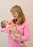 Den lyckliga unga kvinnan rymmer på baby'sens händer Arkivbilder