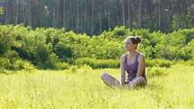 Den lyckliga unga kvinnan sitter på en grön gräsmatta i ett sceniskt fält på en solnedgångbakgrund arkivfilmer