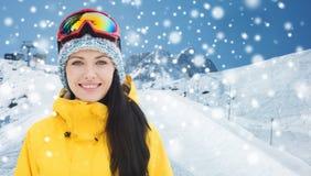 Den lyckliga unga kvinnan skidar in skyddsglasögon över berg Royaltyfri Fotografi