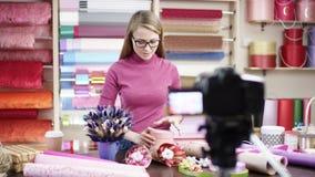 Den lyckliga unga kvinnan som blomsterhandlare i en blomsterhandel planlägger och skapar ordningar av blommor Den lyckliga kvinna arkivfilmer