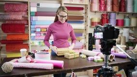 Den lyckliga unga kvinnan som blomsterhandlare i en blomsterhandel planlägger och skapar ordningar av blommor i kransar, buketter lager videofilmer