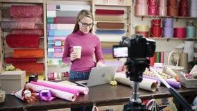 Den lyckliga unga kvinnan som blomsterhandlare i en blomsterhandel planlägger och skapar ordningar av blommor i kransar, buketter stock video