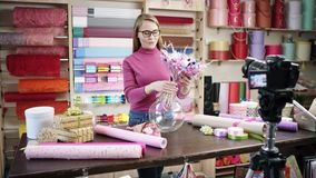 Den lyckliga unga kvinnan som blomsterhandlare i en blomsterhandel planlägger och skapar ordningar av blommor i kransar, buketter arkivfilmer
