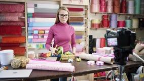 Den lyckliga unga kvinnan som blomsterhandlare i en blomsterhandel planlägger och skapar ordningar av blommor i kransar, vaser oc stock video