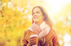 Den lyckliga unga kvinnan som dricker kaffe i höst, parkerar Royaltyfria Bilder
