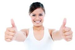 Den lyckliga unga kvinnan som ger tum göra en gest upp Royaltyfria Bilder