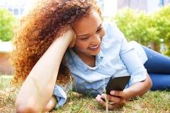 Den lyckliga unga kvinnan som ligger i gräs på, parkerar och ser mobiltelefonen royaltyfri foto