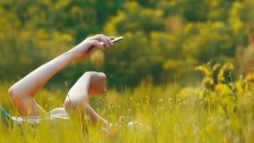 Den lyckliga unga kvinnan som ligger på grön gräsmatta, använder smartphonen på sceniskt fält på solnedgångbakgrund arkivfilmer