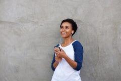 Den lyckliga unga kvinnan som lyssnar till musik med hörlurar och, ilar telefonen Arkivbild