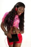 Den lyckliga unga kvinnan som lyssnar till musik med headphonen, fäste till minnestavlaPC:n Royaltyfri Fotografi