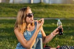 Den lyckliga unga kvinnan som rymmer varm pizza i ask, placerar utomhus- parkerar in royaltyfria foton
