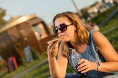 Den lyckliga unga kvinnan som rymmer varm pizza i ask, placerar utomhus- parkerar in royaltyfri foto