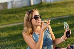 Den lyckliga unga kvinnan som rymmer varm pizza i ask, placerar utomhus- parkerar in fotografering för bildbyråer