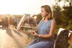 Den lyckliga unga kvinnan som rymmer varm pizza i ask, placerar utomhus- parkerar in arkivbild