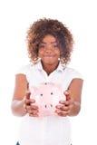 Den lyckliga unga kvinnan sparar pengar i spargrisen Arkivfoton
