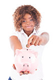 Den lyckliga unga kvinnan sparar pengar i spargrisen Royaltyfria Foton