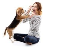 Den lyckliga unga kvinnan spelar med valpen royaltyfri foto