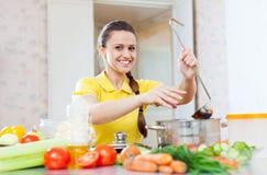 Den lyckliga unga kvinnan tillfogar kryddan i kastrull Royaltyfria Foton