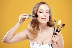 Den lyckliga unga kvinnan tycker om en uppsättning av makeupborstar Glad flickamakeupkonstnär royaltyfri fotografi