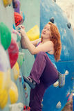 Den lyckliga unga kvinnan vaggar klättring Färgrik rolig inomhus vägg Arkivfoto
