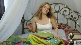 Den lyckliga unga kvinnan vaknar upp och dansen på säng hemma långsam rörelse