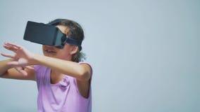 Den lyckliga unga lilla flickan som använder 3d, rullar med ögonen en virtuell verklighethörlurar med mikrofon Förvånad kvinna me arkivfilmer