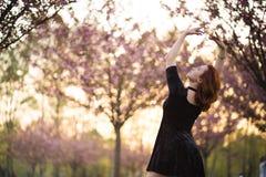 Den lyckliga unga loppdansarekvinnan som tycker om fri tid i en sakura k?rsb?rblomning, parkerar - den Caucasian vita r?dh?rig ma arkivfoton