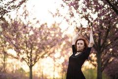 Den lyckliga unga loppdansarekvinnan som tycker om fri tid i en sakura k?rsb?rblomning, parkerar - den Caucasian vita r?dh?rig ma fotografering för bildbyråer