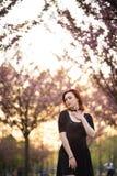 Den lyckliga unga loppdansarekvinnan som tycker om fri tid i en sakura k?rsb?rblomning, parkerar - den Caucasian vita r?dh?rig ma royaltyfri bild