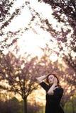 Den lyckliga unga loppdansarekvinnan som tycker om fri tid i en sakura k?rsb?rblomning, parkerar - den Caucasian vita r?dh?rig ma royaltyfria bilder