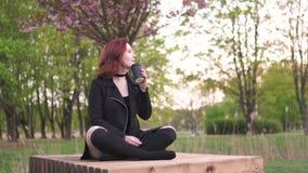 Den lyckliga unga loppdansarekvinnan som tycker om fri tid i en sakura k?rsb?rblomning, parkerar - den Caucasian vita r?dh?rig ma lager videofilmer