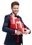 Den lyckliga unga mannen bär presents för en radda royaltyfria bilder