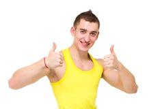 Den lyckliga unga mannen med tum göra en gest upp Royaltyfri Bild