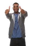 Den lyckliga unga mannen med tum göra en gest upp Fotografering för Bildbyråer