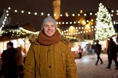 Den lyckliga unga mannen på jul marknadsför i vinter Arkivfoto