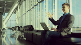 Den lyckliga unga mannen skriver något på hans bärbar dator, medan sitta i flygplats lager videofilmer
