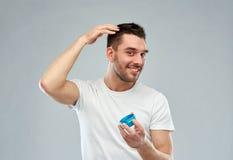 Den lyckliga unga mannen som utformar hans hår med vaxet eller, stelnar Fotografering för Bildbyråer