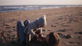 Den lyckliga unga modern i höstkläder som ligger på hennes baksida på sanden och omfamnar happilly, hennes barn, lyfter på upp he arkivfilmer