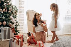 Den lyckliga unga modern med blomman i hennes hår och hennes lilla dotter i trevlig klänning sitter nära det nya årets träd  arkivbilder